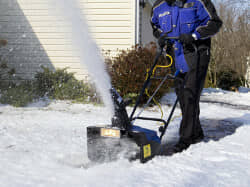 A man clearing the yard with a snow blower